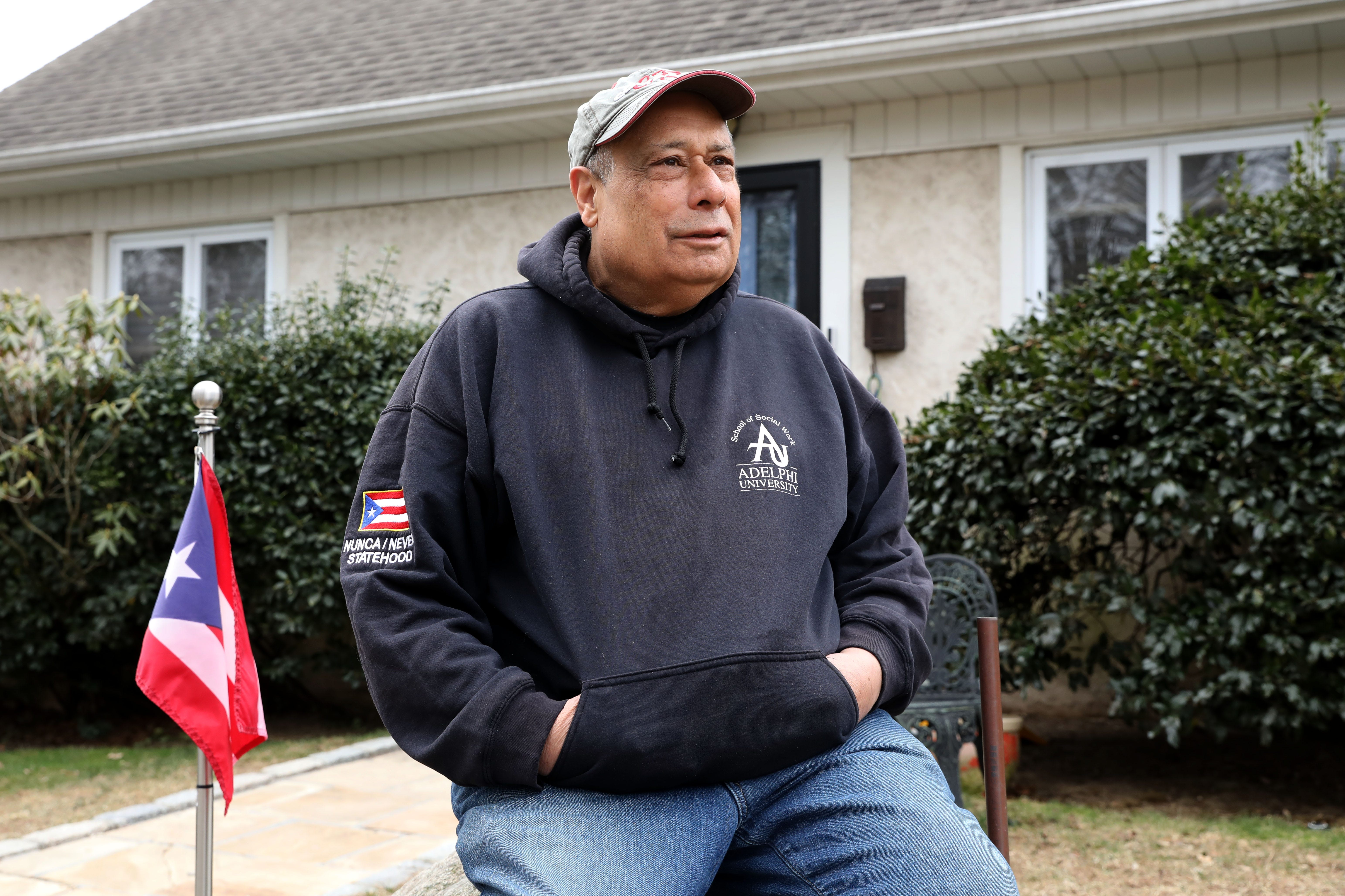 Activist and educator Luis Quiros sits outside his home in Mamaroneck March 16, 2021. Quiros, a proud Puerto Rican, sits beside a Puerto Rican flag that his neighbor asked him to take down and replace with the United States flag.
