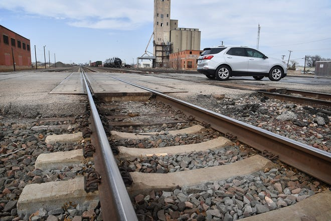 A car drives across the nine-track railroad crossing at Seventh Street. The rough crossing will be rebuilt this summer, according to action taken during Tuesday's City Council meeting.