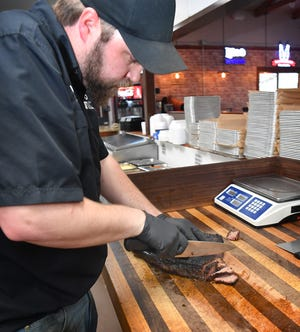 Russell Prickett, executive chef for Post Oak BBQ, slices into a smoked brisket. The Burkburnett restaurant was reviewed by the barbecue editor of Texas Monthly magazine recently.