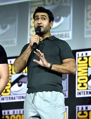 """Eternals"" star Kumail Nanjiani speaking on stage at San Diego Comic-Con in 2019."