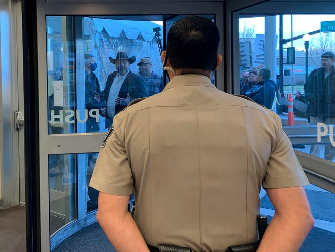 Anti-government activist Ammon Bundy, wearing a cowboy hat, yells through the closed Ada County Courthouse door at law enforcement officers inside Monday, March 15, 2021, in Boise, Idaho.
