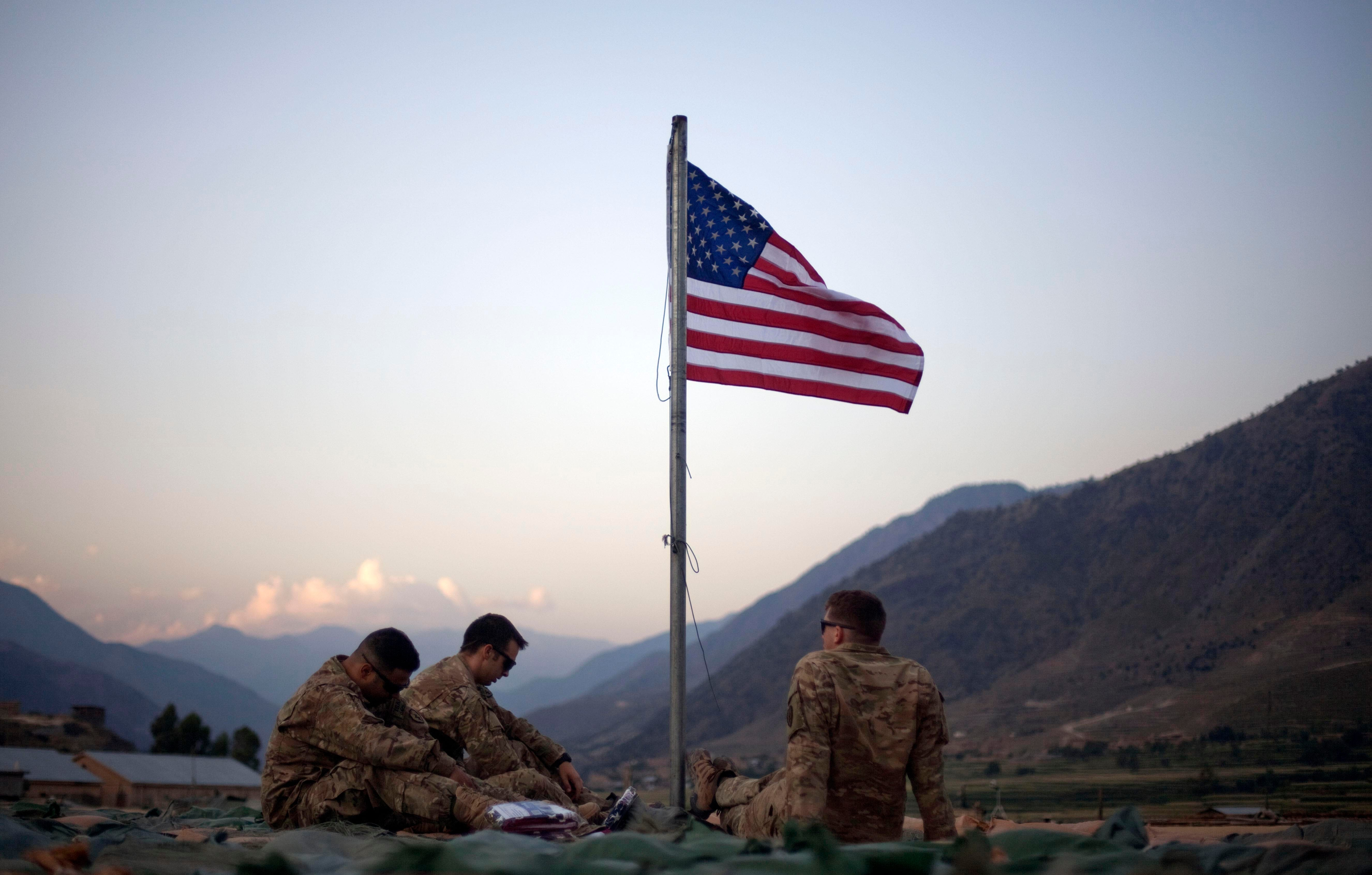 U.S. soldiers sit beneath an American flag just raised to commemorate the tenth anniversary of the 9/11 attacks at Forward Operating Base Bostick in Kunar province, Afghanistan, in 2011. Ten years later, U.S. troops are still in the country.