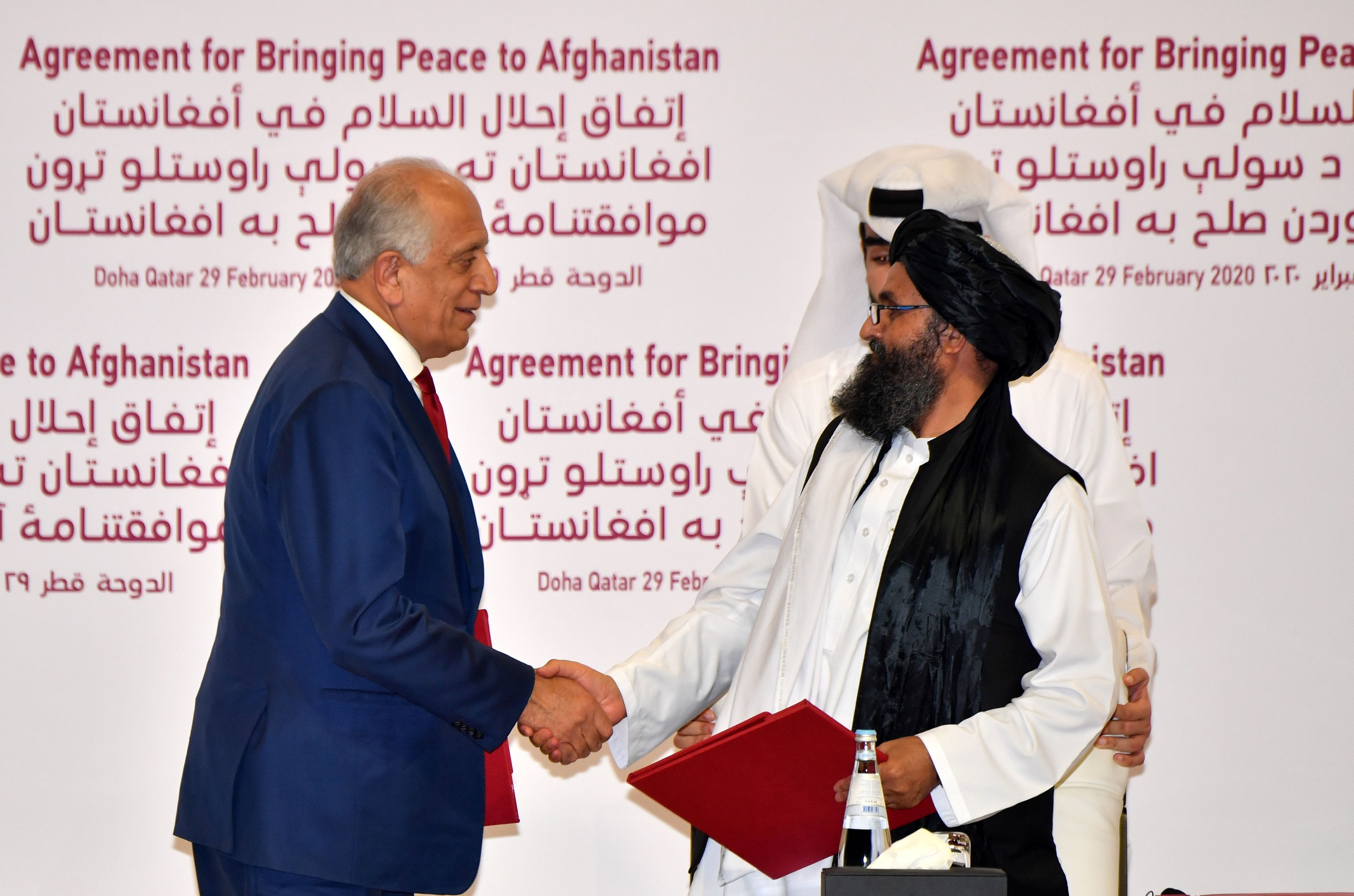 U.S. Special Representative for Afghanistan Reconciliation Zalmay Khalilzad and Taliban co-founder Mullah Abdul Ghani Baradar shake hands after signing a peace agreement Feb. 29, 2020, during a ceremony in the Qatari capital Doha.