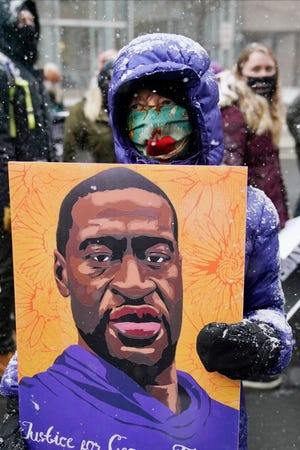 A protester carries a portrait of George Floyd during a protest march around the Hennepin County Government Center, Monday, March 15, 2021, in Minneapolis where the second week of jury selection continues in the trial for former Minneapolis police officer Derek Chauvin. Chauvin is charged with murder in the death of George Floyd during an arrest last may in Minneapolis.