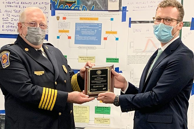 Travis County Emergency Services District No. 2 Chief Ron Moellenberg, left, receives a plaque on March 11 from Joel Duke, interim Public Protection Classification oversight officer at the Texas State Fire Marshal's Office. The plaque certifies the Class 1 rating the fire department received from an independent insurance rating agency.
