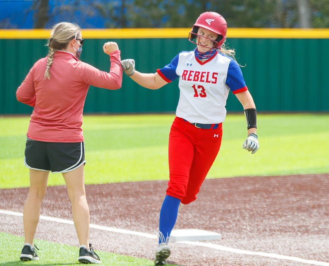 Hays' Katie Noble rounds third base, fist bumping with her coach Lisa Cone, for a three-run home run against Westlake during the Rebels' 4-0 win Tuesday at Westlake High School. Noble tossed a complete-game two-hit shutout with nine strikeouts in the victory.