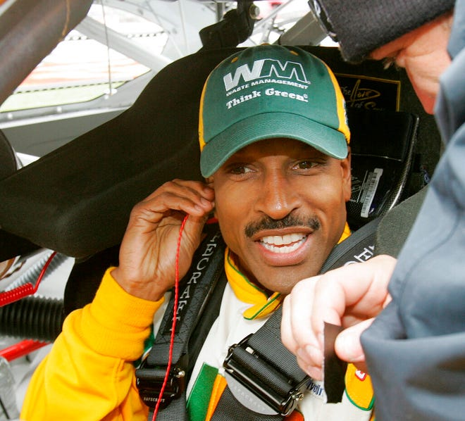 FILE - NASCAR driver Bill Lester gets ready for a rain delayed start of the NASCAR Golden Corral 500 auto race at Atlanta Motor Speedway, in Hampton, Ga., in this Monday, March 20, 2006, file photo. Bill Lester, one of the first Black drivers to compete in NASCAR's Truck Series, will return to competition 14 years after his last start.  Lester will drive for David Gilliland Racing on Saturday, March 20, 2021, in the Truck Series race at Atlanta Motor Speedway. It will be the first NASCAR start for the 60-year-old since 2007. (AP Photo/Ric Feld, File)