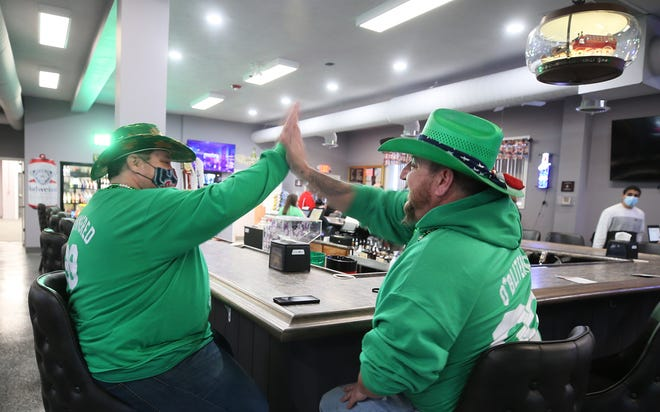 Tom Young and Clint Petroff, social members of Barberton VFW Post 1066, high five each other at the reopening on St. Patrick's Day in Barberton. The VFW post gutted after a fire on May 23, 2020.
