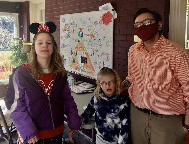 Jocelyn Burkholder, 10, and Lyra Christensen, 8, stand with their educational pod teacher, Declan McCaslin.