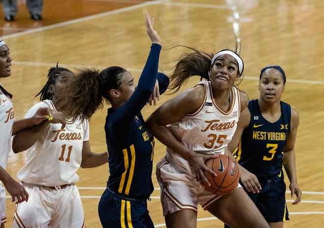 Texas forward Charli Collier (35) pulls down an offensive rebound as West Virginia's Esmery Martinez (12) and Kirsten Deans (3) defend in Austin on Feb. 6, 2021. Collier was been named to the Associated Press' All-American team.