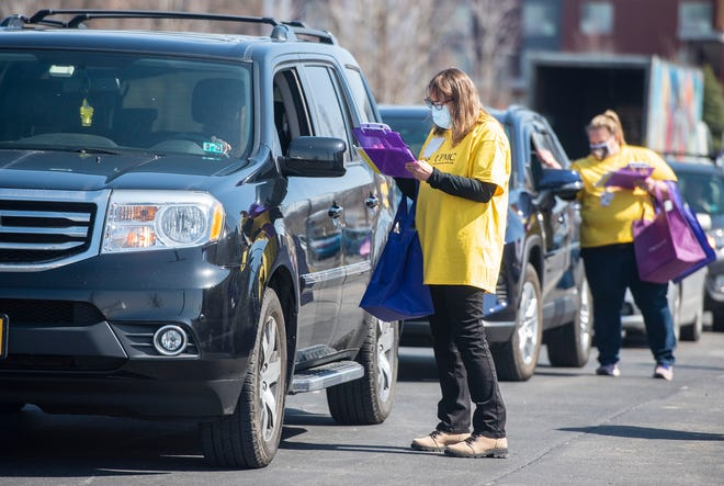UPMC employees take information from patients who registered to receive COVID-19 vaccines at a drive-through clinic set up in the parking lot of the UPMC Lemieux Sports Complex Wednesday in Cranberry Township.