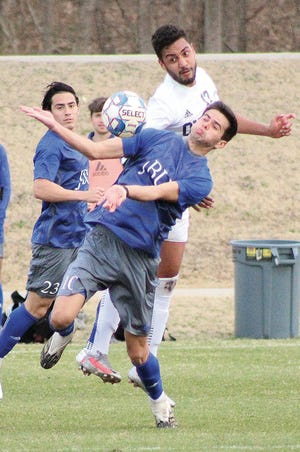 Oklahoma Wesleyan University's Alfeu Bertini, No. 17, challenges a John Brown University player, right, for the ball during men's soccer action earlier this month in Bartlesville.