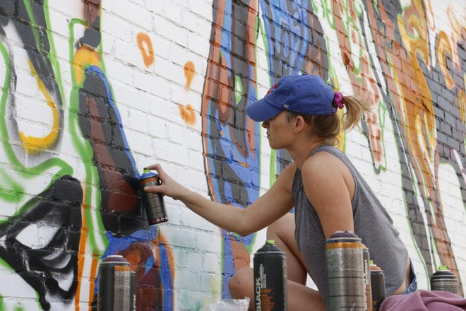 Calina Mishay is pictured Tuesday at Pat Coursey Park as she applies paint to a mural depicting wild horses running through water.