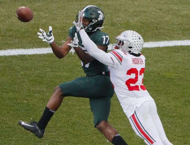 Ohio State Buckeyes safety Marcus Hooker (23) breaks up a pass in the end zone intended for Michigan State Spartans wide receiver Tre Mosley (17) during the fourth quarter of a NCAA Division I football game between the Michigan State Spartans and the Ohio State Buckeyes on Saturday, Dec. 5, 2020 at Spartan Stadium in East Lansing, Michigan.