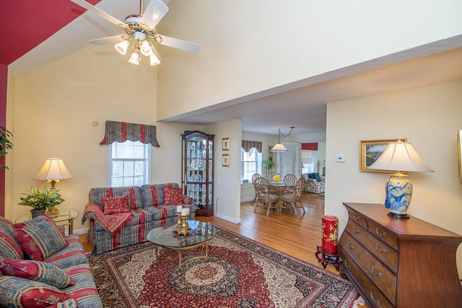 The formal living room at 28 Quashnet Woods Drive, a quiet little cul-de-sac off Route 28, has cathedral ceilings and one burgundy wall to add a cozy touch. Visit the home at an open house from 11 a.m. to 1 p.m. Sunday. [Colin Veitch/Harbor Light Photography]