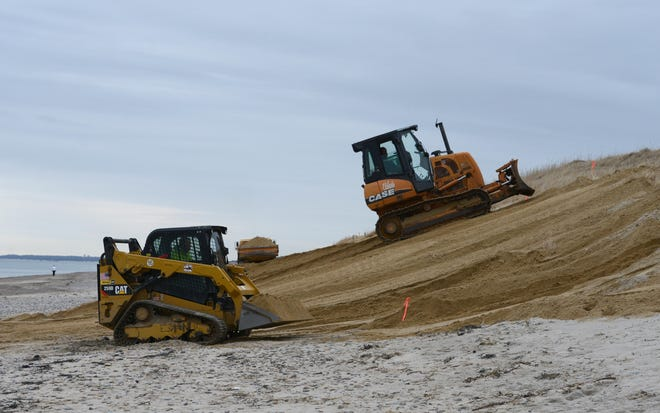 Sand is smoothed out at Sandy Neck Beach, as work continued Wednesday to repair the dune fronting the main parking lot after erosion from winter storms. STEVE HEASLIP/CAPE COD TIMES