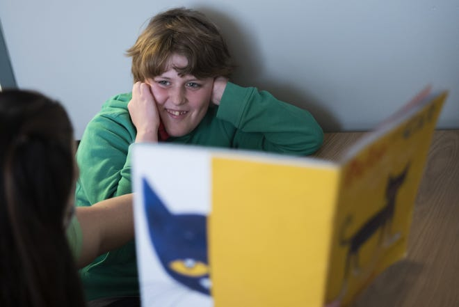 Fourth-grader Luke Moran laughs while reading a Pete the Cat book with his speech therapist, Erin Leasor last month at Bridgeway Academy in Columbus. The school serves students with autism and other developmental special needs.