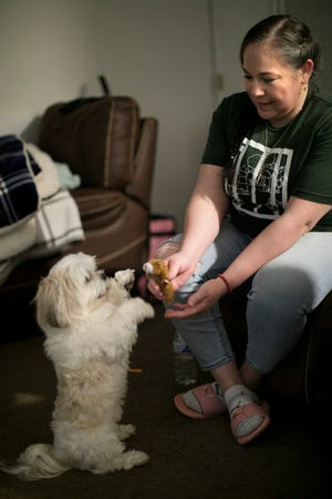 Edith Espinal, playing recently with her dog Bella after dinner at her West Side home, is no longer living in sanctuary at a Columbus church, but she still faces a$59,126fine that Immigration and Customs Enforcementlevied against her last year.