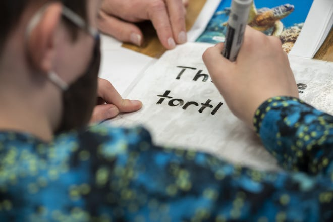 Fourth-grader Aiden Nance practices his writing at Bridgeway Academy. The school recently moved into a larger building on the East Side, despite challenges posed by the COVID-19 pandemic.
