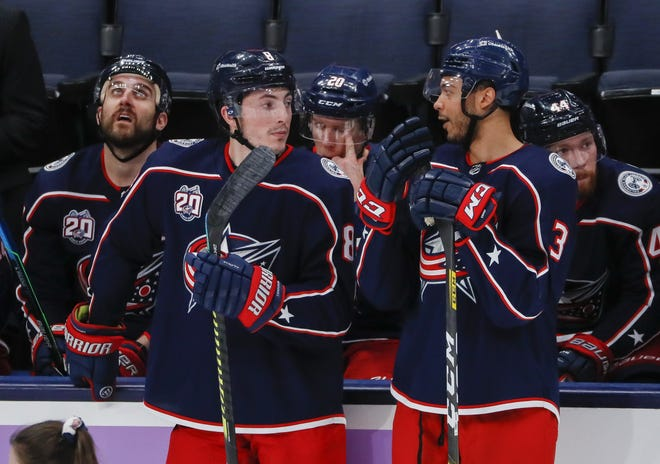 Blue Jackets defensemen Zach Werenski (8) and Seth Jones (3), here discussing strategy during a break in a February game, are playing with more consistency in recent games, according to coach John Tortorella.
