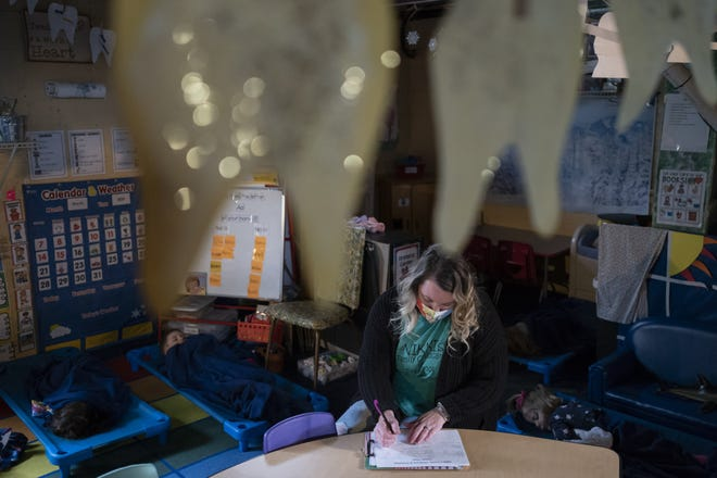As kids nap, Nikki Wells does some administrative work Tuesday at Nikki's Family Childcare and Preschool in Gnadenhutten.