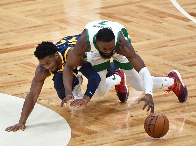 Mar 16, 2021; Boston, Massachusetts, USA; Boston Celtics guard Jaylen Brown (right) and Utah Jazz guard Donovan Mitchell (left) battle for a loose ball during the first half at TD Garden.