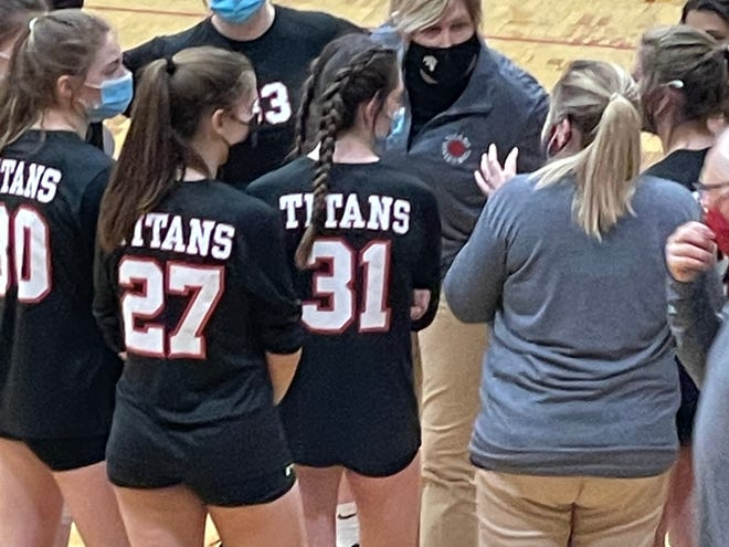 West Hancock high school volleyball coach Melissa Freesmeier (center) gives instructions to her team during Tuesday's season opener at Hamilton, Illinois.