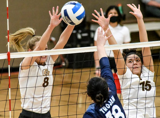 Garden City Community College's Reagan Karlin, left, knocks the ball back to the Colby side on a hit by the Trojans' Savannah Adams as Karlin and teammate Pulelehua Keb go up for a block Tuesday at Perryman Athletic Complex.