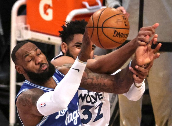 Los Angeles Lakers forward LeBron James (23) and Minnesota Timberwolves center Karl-Anthony Towns (32) battle for a loose ball in the first half on Tuesday, March 16, 2021, at Staples Center in Los Angeles.