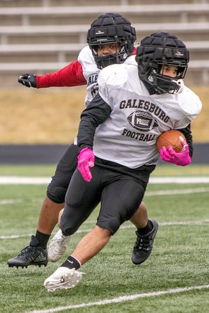 Galesburg High School junior Kyron Leath eludes fellow junior and teammate Jermany Goods during football practice on Tuesday, March 16, 2021 at Van Dyke Field.