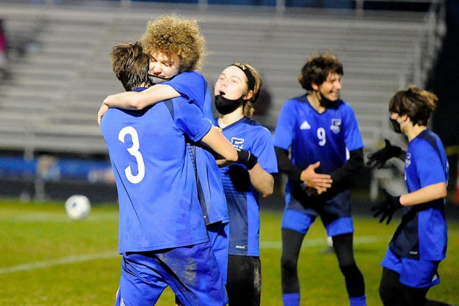 Polk County's Cole Pereira embraces Matias Akers (3) after scoring what proved to be the winning goal in Tuesday's playoff match at Polk.