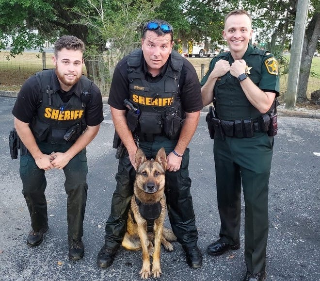 Polk County Sheriff's Deputy Paul Wright and K-9 Albi caught suspected burglar Christopher Lee Howard on Monday. They say Howard tried to drown Albi before Wright pulled his dog away from Howard. Deputy John Raczynski, left, and Deouty Charles Wallace, not pictured, then took him into custody. Major Ian Floyd, right, assisted.