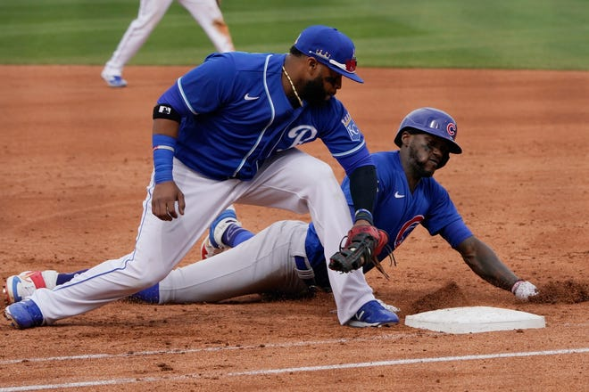 Kansas City Royals first baseman Carlos Santana, left, tags out Chicago Cubs' Cameron Maybin on a pickoff in the fourth inning of a spring training baseball game Saturday, March 13, 2021, in Surprise, Ariz.