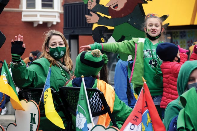 Representatives of the Fitzgerald family wave to spectators Wednesday during the St. Patrick's Day Parade in downtown Leavenworth.