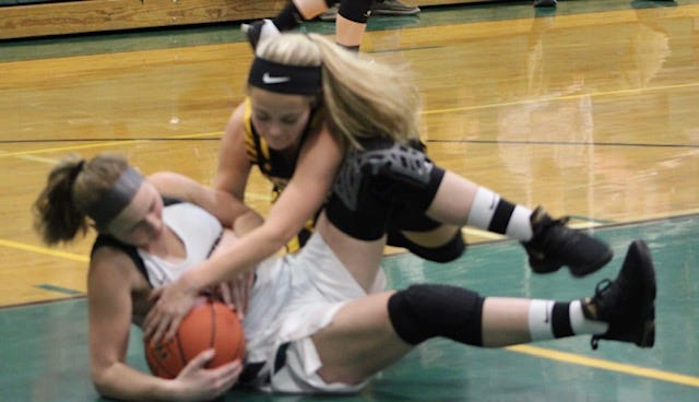 Keyser's Maddy Broadwater fights for the ball against her Hampshire opponent. Broadwater led all scorers with a game-high 15-point performance.
