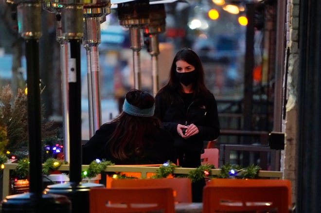 A server wears a face mask while tending to a patron sitting in the outdoor patio of a sushi restaurant in downtown Denver. Restaurants devastated by the coronavirus outbreak are getting a lifeline from President Biden's pandemic relief package. [AP File Photo/David Zalubowski]
