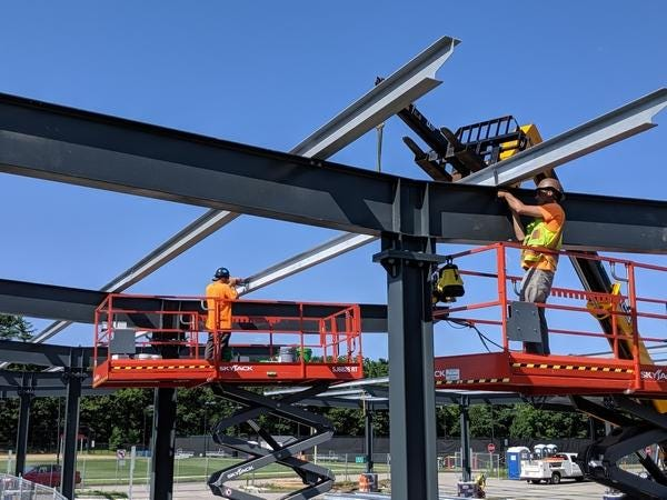 Construction crews in the summer of 2019 at work installing purlins for a solar panel project planned for Natick High School.