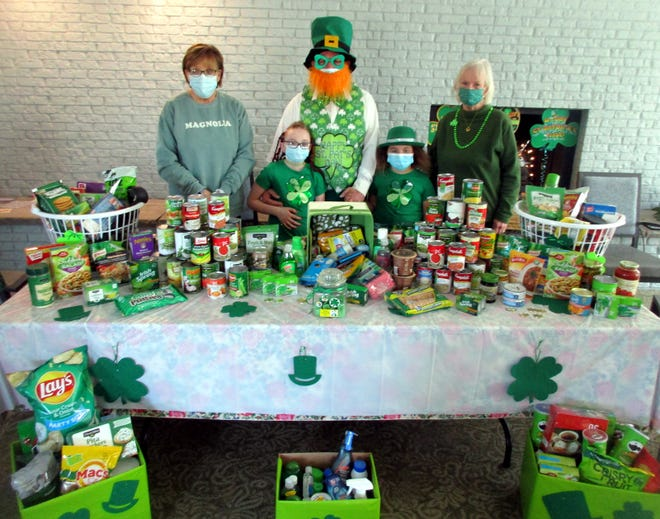 Celebrating St. Patrick's Day March 17 at Madison Lane Apartments in Hamilton are, front row from left, Remi Spencer and Harley Spencer and, back row from left, Hamilton Food Cupboard director Suzanne Collins, resident leprechaun Dave Morgan and tenant representative Gert Federici. Residents and board members of the senior citizen housing complex celebrated the holiday with a food donation drive to benefit the Food Cupboard.
