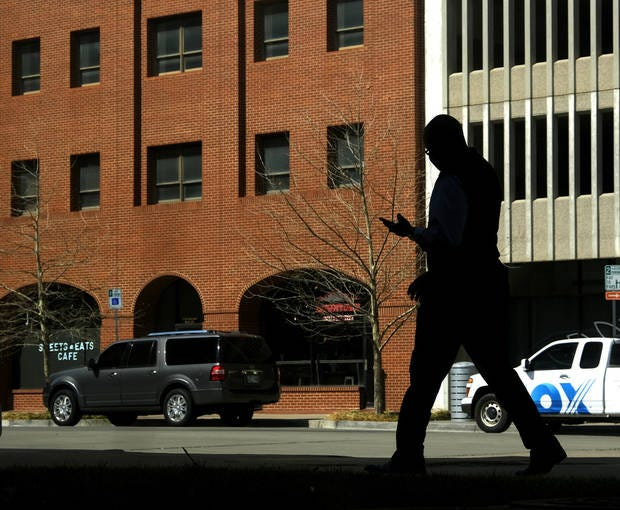 A man walks along Main St. looking at his phone Tuesday, March 9, 2021. Rain is expected to give way to a sunny weekend in Oklahoma City. [Doug Hoke/The Oklahoman]