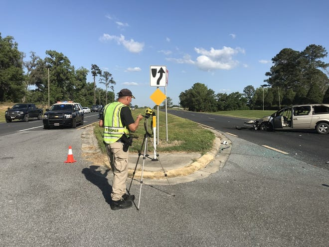 A Florida Highway Patrol traffic homicide investigator takes measurements of the scene of a two-vehicle crash Wednesday that killed two people and seriously injured a third.