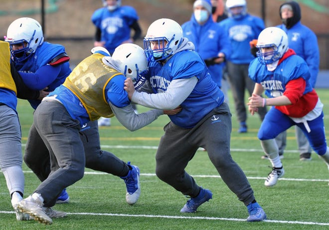 Scituate football player Michael Sheskey, center, blocks during a drill on Tuesday, March 16, 2021.