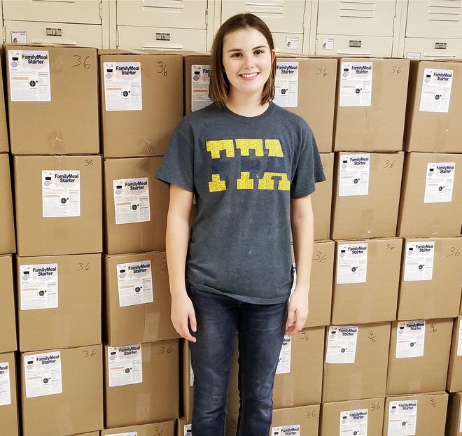 Libby Larkin stands in front of meals packaged at one of her events. Larkin is a state finalist in the area of Service Learning in FFA competition.