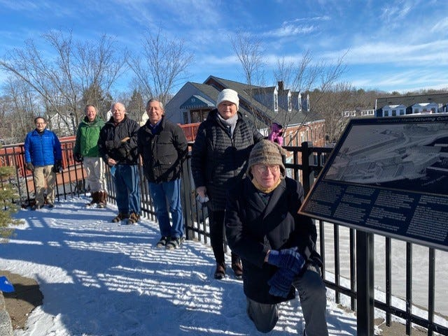 Newmarket Main Street Corporation members gather for the installation of a new bronze plaque, which features an artist's rendering of the mill buildings and a brief account of the town's mill history. The plaque is one of 18 that the group has been installing around town for the past decade. Shown here, front to back, artist R.P. Hale of Concord; NMSC board members Janice Galloway, Bob LeGault, David LeGault, Mike Hoffman, and Ranan Cohen. Not shown is Jon Nolan.