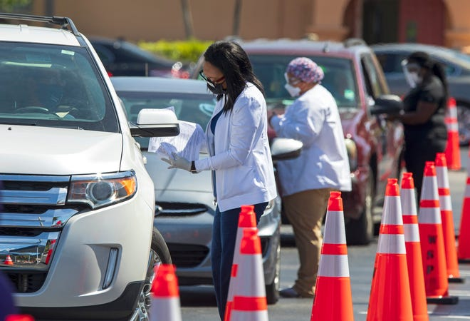 People line up for their second shot  of Covid vaccine during a drive through clinic set up at St. Juliana Catholic Church Friday, March 5, 2021.
