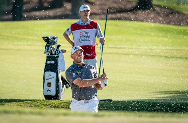 Golfer Lee Westwood blasts out of the sand in front of his his son Sam Westwood during the Honda Classic Pro-Am at the PGA Resort in Palm Beach Gardens, Florida on March 17, 2021.