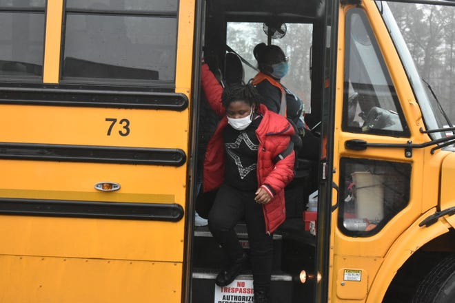 A student exits a school bus at Walnut Hill Elementary on March 16, the first day of in-person instruction after shutting down for COVID-19.