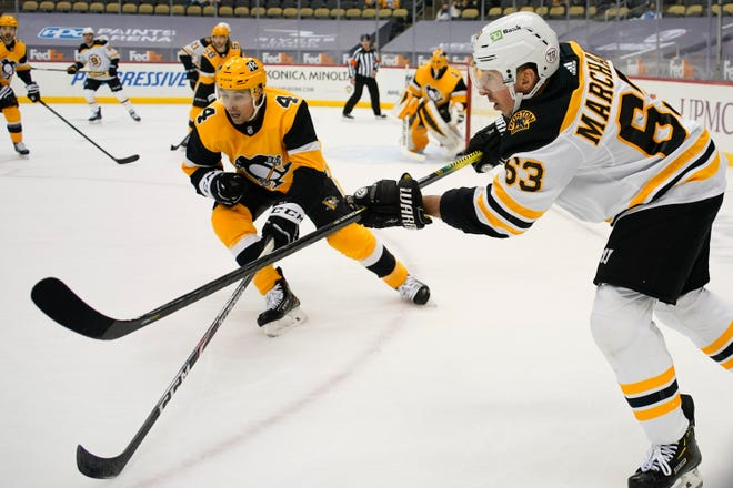 Boston's Brad Marchand passes the puck past Pittsburgh's Cody Ceci during the second period Tuesday night. Boston won, 2-1.
