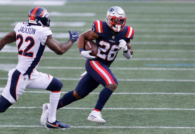 Published Caption:  Patriots running back James White looks for running room as the Broncos' Kareem Jackson closes in during a game at Gillette Stadium in October. Where he will be headed this offseason is uncertain. [The Providence Journal, file / Kris Craig]