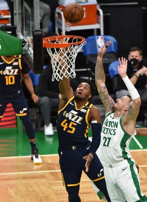 Utah Jazz guard Donovan Mitchell lays the ball in the basket against Celtics center Daniel Theis for two of the 21 points he scored Tuesday night at TD Garden.