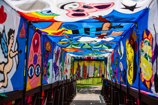 A walkway is surrounded by art at the 2019 Smoky Hill River Festival.
